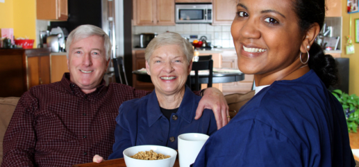 caregiver serving meal to elderly couple