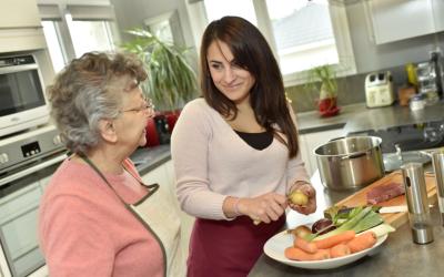 caregiver preparing meal for elderly woman