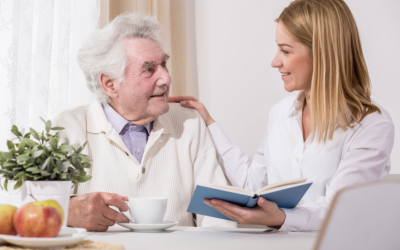 caregiver holding a book with elderly man drinking coffee